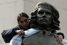 <p>Homem coloca bandeira da Argentina em estátua de bronze de 'Che' Guevara, em Buenos Aires. 'Che' é uma figura tão emblemática do século 20, que a sua imagem transcende a sua ideologia. Photo by Marcos Brindicci</p>