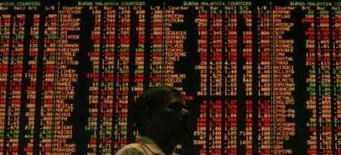 <p>Investidore monitora a bolsa em em galeria em Kuala Lumpur, em foto de 17 de junho. As principais bolsas asiáticas recuaram nesta terça-feira após o Dow Jones fechar em seu pior nível em três meses, fomentando temores de um recuo na demanda de exportações com os preços do petróleo se mantendo alto. Photo by Bazuki Muhammad</p>