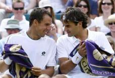 <p>O tenista suíço Roger Federer (dir) conversa com o eslovaco Dominik Hrbaty durante partida pelo torneio de Wimbledon, dia 23 de junho, em Londres. Tenista número um do mundo, Federer iniciou a briga pelo sexto título seguido em Wimbledon com uma vitória por 6-3, 6-2 e 6-2 contra o eslovaco Dominik Hrbaty nesta segunda-feira. Photo by Kevin Lamarque</p>