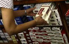 <p>Una vendedora de tabaco en España toma un cartón de cigarrillos en Madrid, 19 jun 2008 (Foto de archivo). Seis de los grandes estudios de cine de Hollywood acordaron el viernes colocar avisos contra el consumo de cigarrillos en las nuevas películas en formato DVD dirigidos a menores, apostando por reducir la influencia de los medios en el uso del tabaco. Los estudios unieron fuerzas con las autoridades sanitarias de California, en lo que fue calificado como un acuerdo sin precedentes para proteger a menores, en Estados Unidos y el resto del mundo, de los riesgos de fumar. (foto de archivo) Photo by (C) JUAN MEDINA / REUTERS/Reuters</p>