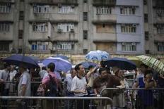 <p>De longues files d'attente se sont formées mardi à Hong Kong devant les succursales de la Banque de Chine plus de vingt-quatre heures avant la mise en circulation d'une série limitée de billets de 20 dollars hongkongais à l'effigie des Jeux olympiques de Pékin. /Photo prise le 15 juillet 2008/REUTERS/Victor Fraile</p>