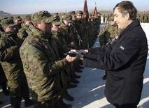 <p>Президент Грузии Михаил Саакашвили вручает карабин M4 одному из солдат на открытии новой военной базы в Гори, 18 января 2008 года. Парламент Грузии одобрил решение об увеличении численности вооруженных сил до 37.000 человек с нынешних 32.000, а также госбюджет страны на 383 миллиона лари ($271,6 миллиона), направив основную часть на расходы оборонного сектора. (REUTERS/Irakli Gedenidze)</p>