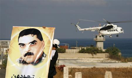 A United Nations helicopter flies in the background as a Hezbollah supporter carries a poster of prisoner Samir Kontar, who is set to be released as part of a prisoner exchange with Israel on Wednesday, in Naqoura near the U.N. headquarters in southern Lebanon July 15, 2008. REUTERS/Ali Hashisho
