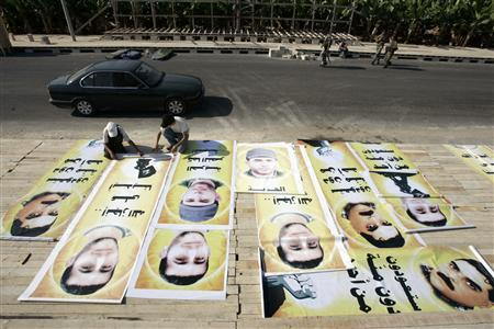 Lebanon's Hezbollah supporters work on posters of prisoners who are set to be released as part of a prisoner exchange with Israel on Wednesday, in Naqoura village near the United Nations headquarters in southern Lebanon July 15, 2008. REUTERS/Ali Hashisho