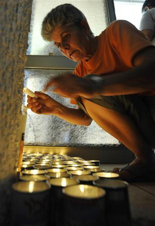 An Israelis woman lights a candle outside the family home of reserve soldier Eldad Regev in the northern city of Kiryat Motzkin July 16, 2008. REUTERS/Amir Cohen