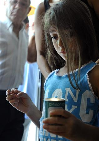 An Israeli girl places a candle outside the family home of reserve soldier Eldad Regev in the northern city of Kiryat Motzkin July 16, 2008. REUTERS/Amir Cohen