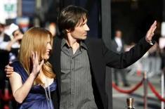 <p>Os atores David Duchovny (direita)) e Gillian Anderson, protagonistas de 'Arquivo X -- Eu Quero Acreditar', acenam para o público durante estréia do filme em Hollywood. Photo by Mario Anzuoni</p>