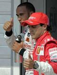 <p>O piloto de Fórmula 1 da equipe McLaren, Lewis Hamilton (esquerda), e o piloto da equipe Ferrari, Felipe Massa, em Budapeste. Hamilton abriu caminho neste sábado para a terceira vitória consecutiva depois de assegurar a pole position do GP da Hungria de Fórmula 1. Photo by Karoly Arvai</p>