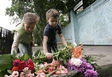 <p>Mosca, bambini depongono fiori davanti alla casa di Alexander Solzhenitsyn, il grande scrittore e dissidente russo morto due giorni fa all'età di 89 anni. REUTERS/Alexander Natruskin</p>