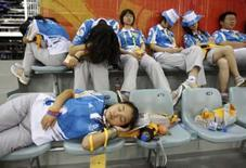 <p>Voluntários descansam durante treino de ciclismo REUTERS. Photo by Jacky Naegelen</p>