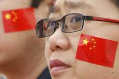 <p>Chinês assiste ao desfile da tocha olímpica, em frente ao portão da praça Tiananmen com uma bandeira da China colada em seu rosto     REUTERS. Photo by Claro Cortes Iv</p>