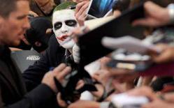 """<p>Un fan truccato da Joker chiede un autografo all'attore Christian Bale, il Batman di """"The Dark Knight"""" alla prima europea del film, il 21 luglio scorso a Londra. REUTERS/Toby Melville</p>"""