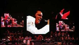 <p>A live band backs up a virtual Elvis during a memorial concert of Elvis footage in Memphis, Tennessee, August 16, 2007. Poor Elvis. Random sightings of the King of Rock 'n' Roll have tapered off in recent years, and now he has mysteriously disappeared from the upper echelons of a new list that ranks the artists with the most No. 1 hits on the U.S. pop singles chart. REUTERS/Lucas Jackson</p>