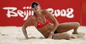 <p>La estadounidense Kerry Walsh yace sobre la arena tras devolverle una pelota a su compañera Misty May-Treanor durante una práctica en el Centro Olímpico del voleibol de playa de Pekín, 6 de agosto del 2008. La popularidad del voleibol de playa ha creado una especie de relación de amor-odio con la televisión. Photo by Carlos Barria/Reuters</p>