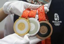 <p>Un membro dello staff del comitato organizzatore dei Giochi di Pechino mostra le tre medaglie: ora, argento e bronzo in palio in questa edizione. REUTERS/Jason Lee</p>