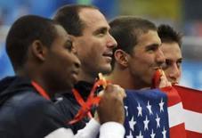 <p>Phelps, Weber-Gale, Jones e Lezak dos Estados Unidos comemoram a medalha de ouroe o novo recorde mundial nos 4x100 metros livre. Photo by Kai Pfaffenbach</p>