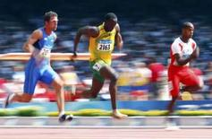 <p>Usain Bolt of Jamaica (centro) disputa sua bateria eliminatória nos 100 metros, no Ninho do Pássaro, em Pequim. Photo by Phil Noble</p>