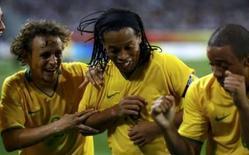 <p>O brasileiro Marcelo (dir) comemora gol contra Camarões junto com Ronaldinho (centro) e Rafinha, dia 16 de agosto. O Brasil está de volta a uma semifinal de Olimpíada no futebol masculino depois de oito anos. Neste sábado, a equipe se vingou de Camarões, seu último algoz olímpico, por 2 x 0, na prorrogação. Photo by Alvin Chan</p>