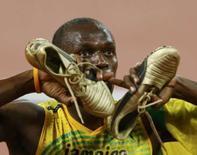 <p>Usain Bolt, da Jamaica, mostra suas sapatilhas douradas depois de ganhar o ouro nos 100 metros e bater o recorde mundial da prova. Photo by Mike Blake</p>