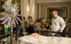 <p>Brazilian writer Joao Ubaldo Ribeiro stands by the body of his friend, singer-songwriter Durival Caymmi, during the wake in Rio de Janeiro August 16, 2008. REUTERS/Bruno Domingos</p>