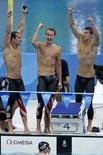 <p>Команда США по плаванию: Брендан Хэнсен (слева) Аарон Пирсол (в центре) Майкл Фелпс (справа) и Джейсон Лезак (в воде) после победы в комбинированном заплыве на 400 метров 17 августа 2008 года. Фелпс таким образом завоевал восьмую золотую медаль на Олимпиаде в Пекине и 14-ю в карьере. REUTERS/Jason Reed</p>