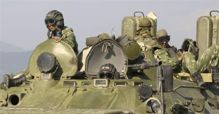 Russian soldiers are seen sitting on an armoured personnel carrier on the outskirts of Gori August 19, 2008. A Russian military column crossed from Georgia back into Russia on Wednesday after Western governments raised pressure for a quick and full pullout under an international ceasefire deal. REUTERS/Adrees Latif