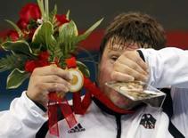 <p>O alemão Matthias Steiner segura a foto de sua esposa Susann ao receber a medalha de ouro no levatamento de peso. Ela morreu pouco antes dos Jogos, em um acidente de carro, e ele prometeu a conquista em homenagem a esposa em seu leito de morte. Photo by Alvin Chan</p>