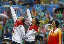 <p>Las medallistas de oro Misty May-Treanor (centro) y Kerri Walsh de Estados Unidos celebran su triunfo sobre el podio luego de la competencia de voleibol de playa femenino en Pekín (21/08/2008). Photo by Carlos Barria/Reuters</p>