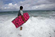 <p>A body boarder stands on the shore at a beach in Havana August 18, 2008. Not long ago, Cuban surfers made surfboards by molding insulation foam from refrigerators with a cheese grater. Now they ride the waves on second-hand surfboards donated by surfers in other countries, whose solidarity is keeping afloat one of the least known tribes in the surfing universe. REUTERS/Claudia Daut</p>