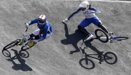 <p>Anne-Caroline Chausson (esq.),da  França, parte para o ouro depois que a britânica  Shanaze Reade, uma das favoritas, caiu ao tentar ultrapassá-la na primeria final do BMX em uma Olimpíada. Photo by Tim Wimborne</p>