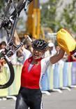 <p>Sabine Spitz, da Alemanha, comemora a medalha de ouro na prova de mountain bike feminino, cruzando a linha de chegada carregando sua bike em uma mão e a bandeira de seu país na outra. Photo by Jacky Naegelen</p>