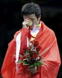 <p>Medalha de ouro do boxe, Zou Shiming se emociona no pódio com a bandeira da China após vencer a categoria até 48 kg, neste domingo. Photo by Lee Jae-Won</p>