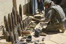 <p>Солдат американской армии изучает конфискованное оружие и боеприпасы в Багдаде, 16 августа 2008 года. США и Ирак договорились о пакте безопасности, согласно которому все американские войска покинут Ирак до конца 2011 года, сообщил в понедельник премьер-министр страны Нури аль-Малики. REUTERS/Ali Shati (IRAQ)</p>