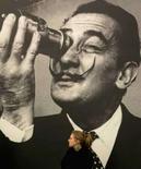 <p>Mulher passa em frente a fotografia do artista espanhol Salvador Dalí em galeria do museu Tate em Londres. Oito décadas passaram desde que Dalí e o cineasta Luis Buñuel mostraram um homem cortando o globo ocular de uma mulher com uma lâmina. Photo by Toby Melville</p>