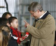 <p>Canadian Prime Minister Stephen Harper waves to a baby 200 km (124 miles) north of the Arctic Circle in Inuvik, Northwest Territories, August 26, 2008. REUTERS/Todd Korol</p>