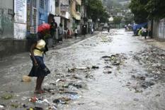 <p>Mulher caminha em maio a enxurrada causada pelo furacão Gustav, em Porto Príncipe, dia 26 de agosto. A tempestade tropical Gustav perdeu força e estacionou sobre o Haiti na quarta-feira, despejando uma quantidade torrencial de chuva sobre o país. Photo by Reuters</p>