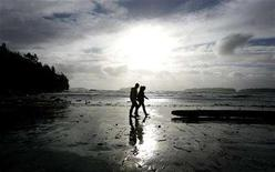 <p>A couple walks along the beach near Tofino, British Columbia February 5, 2006. REUTERS/Finbarr O'Reilly</p>