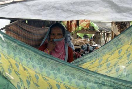 A flood-affected woman watches from inside her makeshift tent at Madhepura town in Bihar August 29, 2008. REUTERS/Krishna Murari Kishan