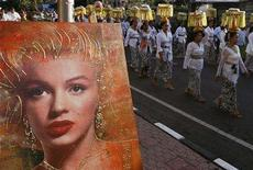 <p>People walk past a portrait of Marilyn Monroe as they carry offerings during a procession of Pelebon or The Royal Cremation Ceremony in Ubud, on the Indonesian island of Bali, July 13, 2008.</p>