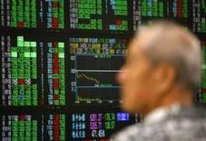 <p>Homem observa monitores do mercado de ações em Taipé, dia 11 de setembro. Os mercados asiáticos caíram amplamente na quinta-feira, com as ações da região com exceção do Japão em seu menor nível desde outubro de 2006, afetados pela persistente instabilidade no setor financeiro. Photo by Nicky Loh</p>