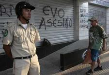 <p>Guarda da prefeitura de Santa Cruz em frente a pichação que diz 'Evo assassino'. Photo by David Mercado</p>