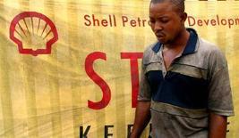 """<p>Мужчина проходит мимо эмблемы Royal Dutch Shell в столице Нигерии Лагосе, 12 января 2006 года Нигерийские боевики """"Движения за освобождение дельты реки Нигер"""" атаковали принадлежащий Royal Dutch Shell объект нефтяной инфраструктуры в понедельник. REUTERS/George Esiri</p>"""