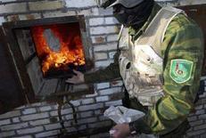 <p>Сотрудник туркменской службы по контролю за оборотом наркотиков бросает в печь пакет с опиумом в городе Маныш, в 20 километрах от Ашхабада, 7 февраля 2007 года. Российские МВД и ФСБ не смогли немедленно прокомментировать сообщения туркменских правозащитников, утверждающих, что российский спецназ помог туркменским спецслужбам в перестрелке задержать банду в Ашхабаде. REUTERS/Michael Steen</p>