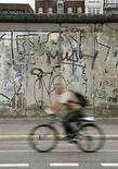 <p>Un ciclista pasea por la ruta junto al antiguo muro de Berlín, 12 ago 2007. Cuatro graffiti que cubrían gigantes placas del muro de Berlín podrían alcanzar un precio de hasta 3.000 euros (4.350 dólares) cada uno cuando salgan a la venta el viernes, dijo el jueves una casa de subastas de la capital alemana. Los cuatro bloques de 2,8 toneladas provenientes del muro que dividió a la capital alemana en la zona comunista del este y la capitalista de occidente son trozos de la historia germana, afirmó Hans Peter Plettner, portavoz de Deutsche Grundstuecksauktionen AG. Photo by (C) ARND WIEGMANN / REUTERS/Reuters</p>