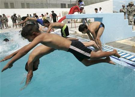 Boys jump into the newly-opened Mithaq swimming pool in Baghdad's Sadr City August 30, 2008. REUTERS/Thaier al-Sudani
