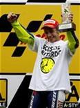 <p>Il pilota Yamaha Valentinao Rossi alza il suo trofeo dopo aver vinto il suo quinto titolo del mondo in Giappone. REUTERS/Toru Hanai</p>
