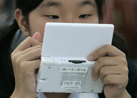 A student uses English-learning software on a Nintendo DS during a media event at Tokyo Girls Junior High School in Tokyo June 26, 2008. REUTERS/Michael Caronna