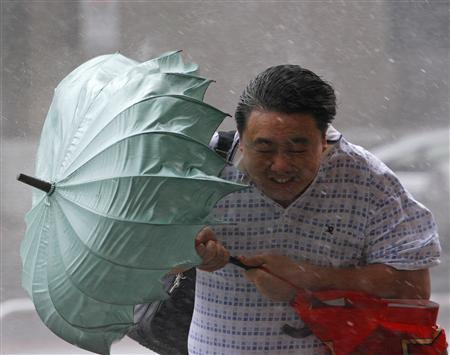 A man struggles against the wind with his umbrella as Typhoon Jangmi hits Taipei September 28, 2008. REUTERS/Nicky Loh