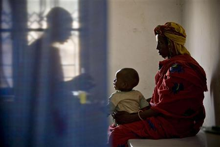 A doctor (L) administers medicine to a sick child at a health clinic run by the medical charity Medecins Sans Frontieres (MSF) Holland in Kerfi, a site for displaced Chadians, some 50 km (30 miles) south of the eastern town of Gos Beida, in this June 10, 2008 file photo. The health crisis in developing countries is, some experts say, being exacerbated by the West as countries relax stringent immigration regulations to attract doctors and nurses from less developed countries to boost their own flagging health systems while saving money on expensive training. To match feature HEALTH-BRAINDRAIN/ REUTERS/Finbarr O'Reilly/Files