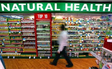 A store worker walks past rows of herbal, vitamin and mineral pill products at a suburban pharmacy in a file photo. REUTERS/David Gray
